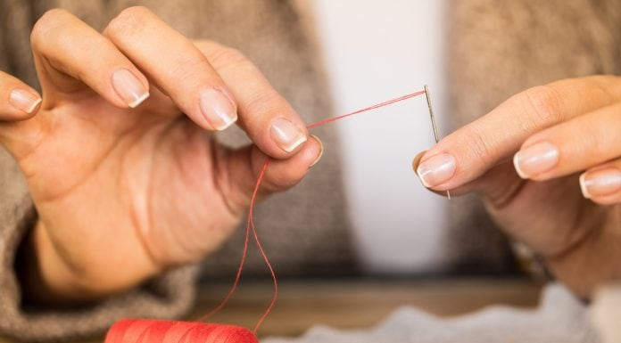 man putting a thread through a needle