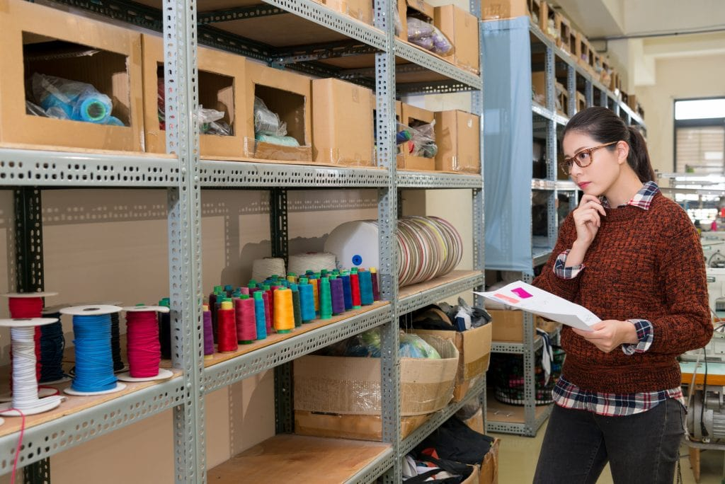 woman analyzing sewing room furniture and accessories on the shelf