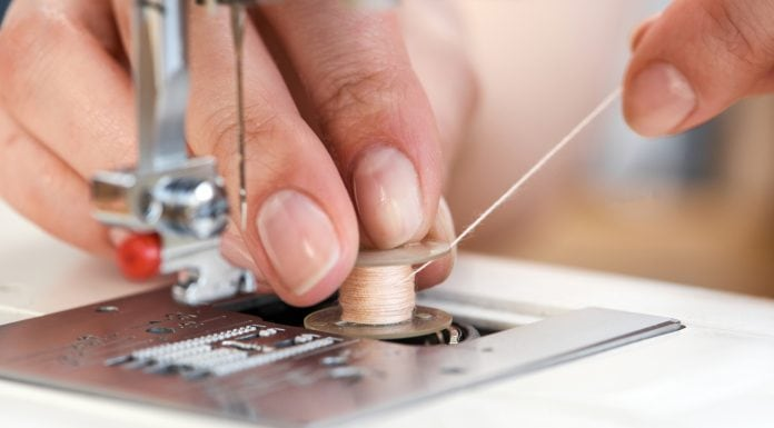 tailor threading a sewing machine seen from close up