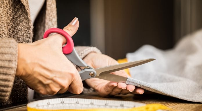 woman cutting fabric with scissors