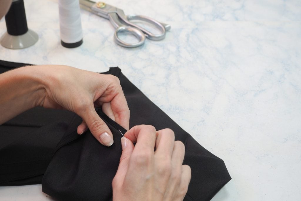 tailor showing how to hem pants by hand