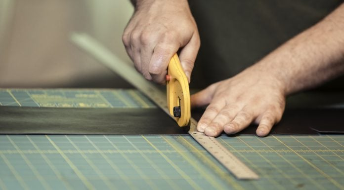 man using a rotary cutter on a piece of leather